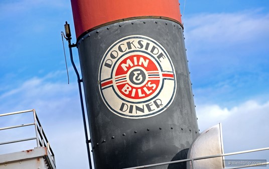 This Min & Bill's Dockside Diner logo appears on a smoke stack on the boat, above the front counter.