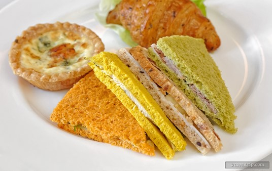 "The sandwiches from The Parisian Afternoon Lunch are too cute!!! From left to right, ""tomato, basil bread sandwich with basil pesto, tomato, carrot and cucumber"", ""curry, turmeric bread sandwich with garlic aioli and chicken"", ""multi grain, cranberry bread sandwich with mayonnaise, apple and turkey"", and ""tarragon, spinach bread sandwich with mustard tarragon butter and ham""."