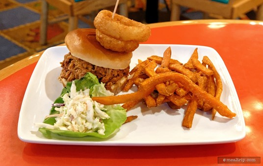 Slow-smoked Pulled Pork Sandwich                on a Brioche Roll with Onion Rings, Barbecue Sauce, and Western Slaw 