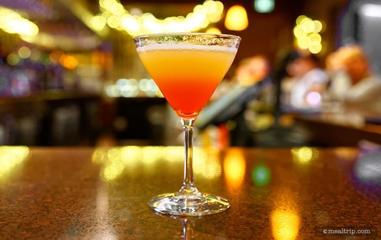 """The featured beverage at the """"first course stop"""" is a Bay Lake Sunset, which is generally only available to guests that have access to the exclusive Top of the World Lounge in the Bay Lake Tower complex."""