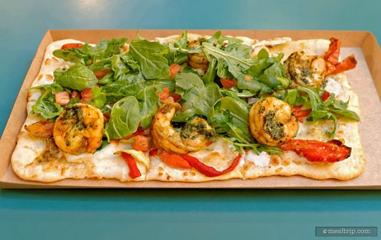 The Shrimp Flatbread at Animal Kingdom's Pizzafari features Roasted Shrimp, Tomato, Red Pepper, Alfredo Sauce and a Savory Pesto (which is smeared on the shrimp) and topped with Arugula.