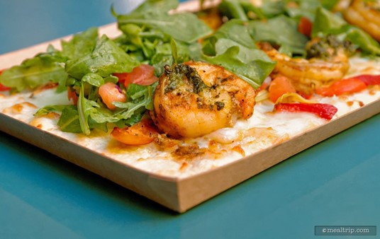 """A closeup of a shrimp on the Shrimp Flatbread reveals that the """"savory pesto"""" that's listed on the menu, is actually smeared on each shrimp."""
