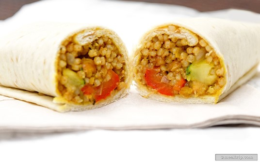 The Roasted Vegetable Couscous Wrap at Anandapur Local Foods Cafe  features roasted vegetables and couscous wrapped in Lavash bread with a  side cup of lemon herb yogurt sauce.