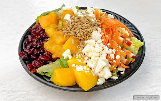 Mango Joe's Fruit Salad combines a generous portion of fresh cut mangos  with dried cranberries, feta cheese, sunflower seeds, sliced carrots,  diced apples, and lettuce.