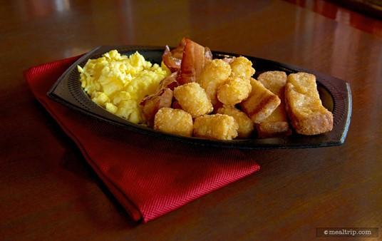 Seafire Inn's breakfast platter with scrambled eggs, bacon, potato hash poppers, and fresh toast sticks.