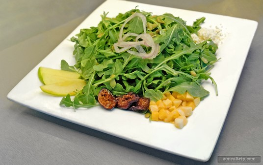 Sharks Signature Salad contains arugula greens with mango, pear, pumpkin seeds, gorgonzola cheese, figs, and onions with a house-made honey mustard vinaigrette.