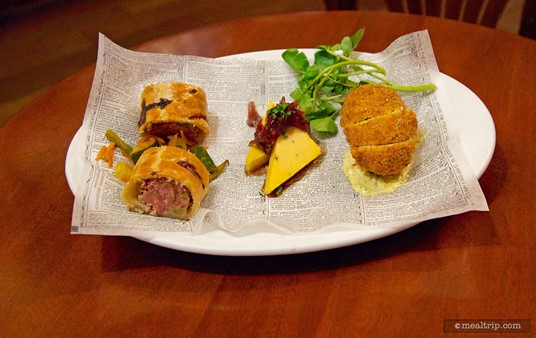 Tapas-sized sampling of Pork and Apple Sausage Roll with House-made  Piccalilli, Cotswolds Cheddar with honey and onion jam, and a Scotch Egg  with mustard.