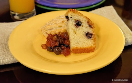 A slice of blueberry bread, some dark raisin chutney, and a strawberry danish with coarse cut sugar on top are plated.