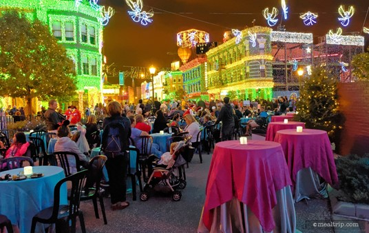"""There are a couple of """"standing"""" tables around the base of the """"joy to the world"""" globe, but there also seems to be enough tables with seats for everyone as well."""