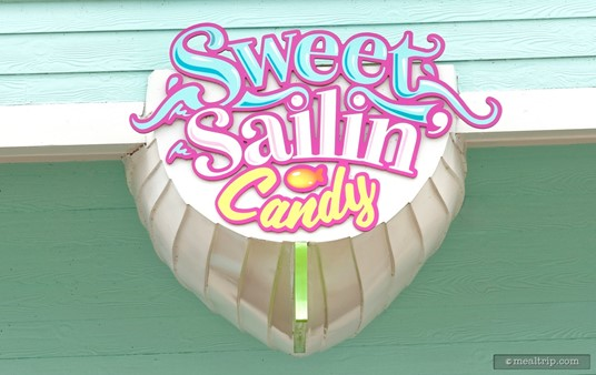 The boat bottom shaped Sweet Sailin' Candy sign that hangs over the front of the shop received a new color system (around 2020, I think). The exterior of the building had been yellow with a thin pink garden script font for the store's name. The building is more of a soft aqua now with a mixed thick font system (that's a little easier to read).