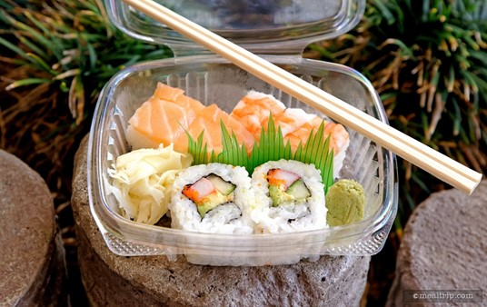 """The """"Combo Sushi""""                                                                                     from Epcot's Kabuki Cafe contains two pieces of California Roll with Salmon, Shrimp Hako-Sush, and a couple of accompaniments like wasabi and ginger. (The green grass in there... is plastic, but very cool looking.)"""