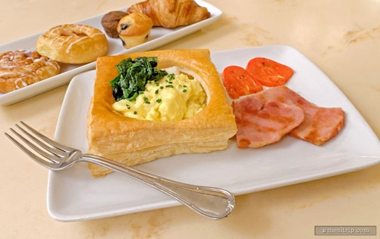The Eggs Florentine on the Be Our Guest Breakfast menu features a puff pastry shell filled with scrambled eggs, cheese, and fresh spinach, and is served with country ham and roasted plum tomatoes.