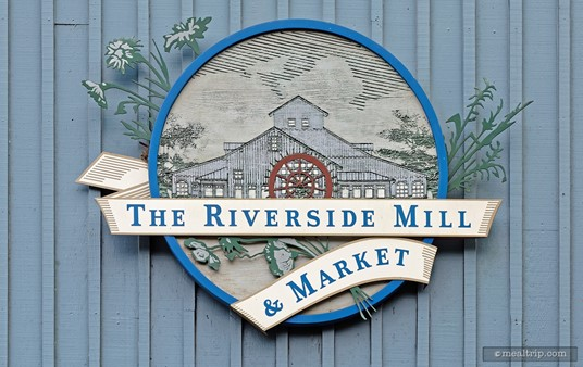"""The exterior Riverside Mill sign hangs on the """"wheel-side"""" of the building, next to the river."""