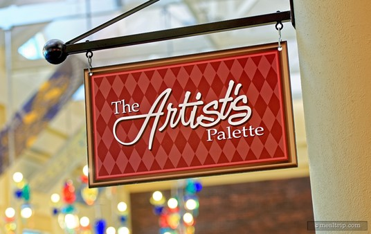 This Artist's Palette sign is located on the inside of the restaurant. The main dining room's colorful glass lighting is shown in the back of the frame.