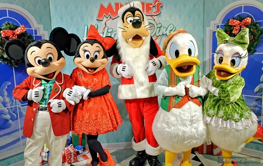Mickey, Minnie, Santa Goofy, Donald, and Daisy are all dressed in their holiday finest at Minnie's Holiday Dine.