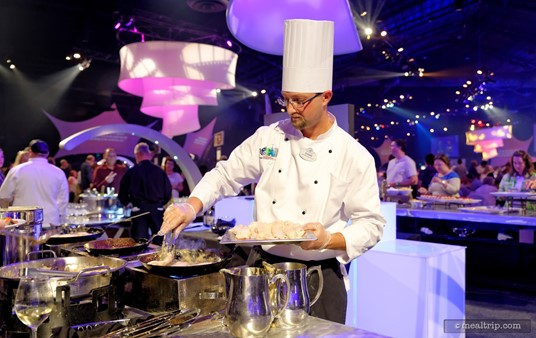 """A Disney chef pan-frying Free Range Chicken Breasts with Meyer Lemon Pan Gravy at the 1901-1924 """"Beginnings - Casual Dinner Station""""."""