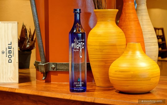 There are colorful displays of modern Mayan art with Tequila bottles throughout the restaurant. Here, a blue Milagro Silver bottle is paired with some orange pottery.