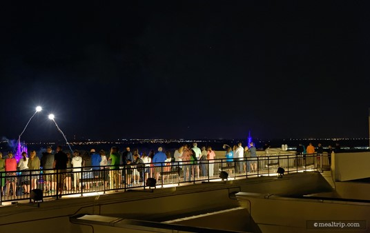 """The """"firework observation deck"""" for California Grill is located on the Magic Kingdom side. You can see the spire """"Cinderella Castle"""" to the far left in this photo (it's purple, just under the two fireworks)."""