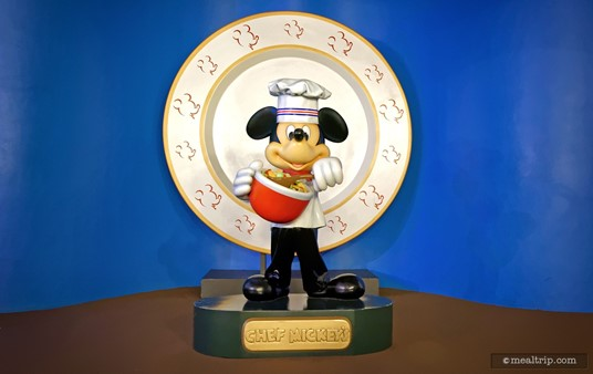"""It's Chef Mickey himself! This statue is for taking pictures with. A PhotoPass photographer is often on-hand as well. The Mickey is slightly smaller than the """"real life"""" version, mostly to better accommodate large group photos."""