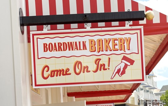 """There are """"BoardWalk Bakery"""" signs up near the awnings."""