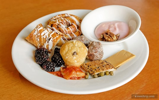 A plate of goodies from the buffet area during an Akershus breakfast including yogurt with pecans, fresh baked goods, and some Norwegian items like Peppered Mackerel, Tomato Herring, Capers and Gjetost Goat Cheese.