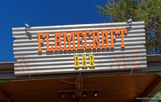 This rustic Flamecraft Bar sign is located on the side of the location.