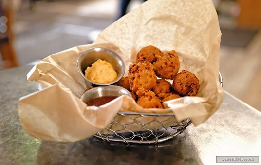 """The """"Bunch of Puppies"""" is a basket full of House-made hushpuppies served with pimento cheese and red jalapeño jelly."""