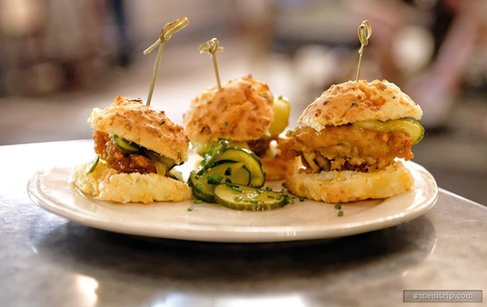 """The Homecomin' """"Thigh High Chicken Biscuits"""" feature three biscuits topped with Chef Art's famous fried chicken thighs and bread and butter pickles. The chicken is also drizzled with a hot honey sauce (which is really a """"medium"""" sauce, in my book of hotness)."""