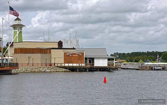 """This an exterior side photo of """"The Boathouse"""" restaurant, as seen from across the """"bay"""" (more or less just past Raintree Forest, on a large bridge)."""