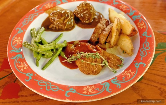 Meatballs in a dark herb sauce, chicken schnitzel, and green beans fill a plate from the Biergarten in Epcot.