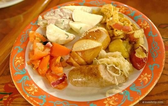 A buffet plate with Biergarten's pretzel bread, sausage, sauerkraut, and potato salad.