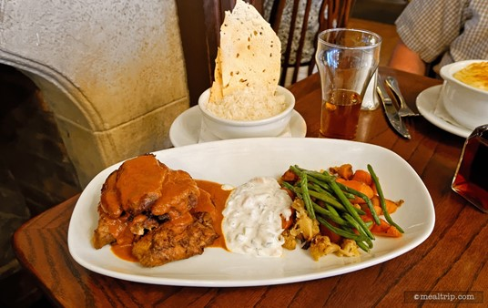 Indian-style Chicken Masala served with cucumber raita, mixed vegetables, and a bowl of basmati rice and crispy poppadom chips.